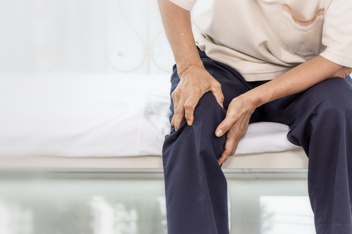 Person holding knee due to pain