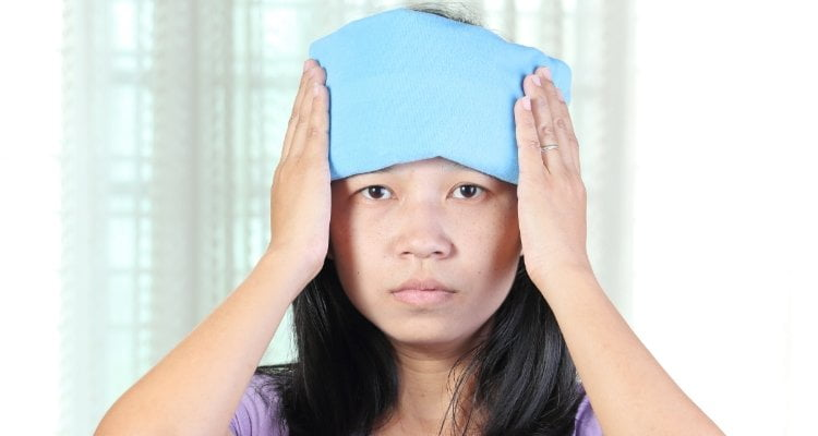 Woman holding heat pad to forehead
